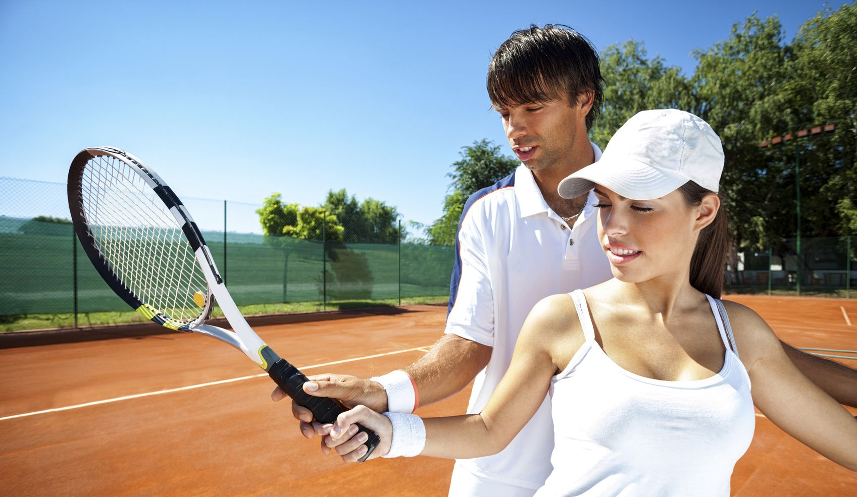 Woman and male tennis instructor practicing racket control on tennis court